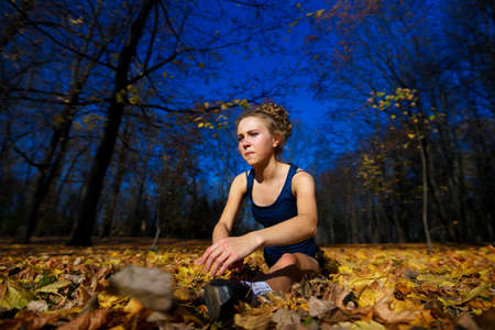 Healthy young woman warming up stretching her arms in the road outdoor, jogging session in park.