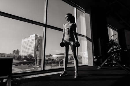 Athletic girl in sportswear performs exercises with a barbell, dumbbells. Fitness, workout, healthy lifestyle