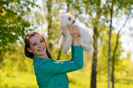 Young woman with her dog. Puppy white dog is running with it's owner. Concept about friendship and animal. Stok Fotoğraf