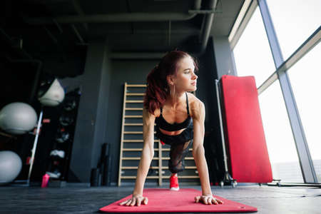 Shot of fitness woman on exercise mat. Female athlete lying on her back doing gym workout