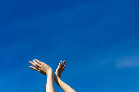 I wish we could touch the sky, female stretching hands to blue sky. Freedom and spring concept