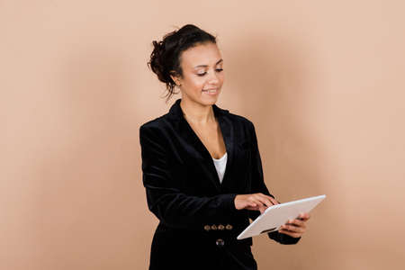 An isolated shot of a happy black businesswoman in studio, notebook, smartphone