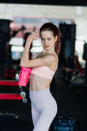 Young female at the gym trainer holding bottle of water Stock fotó