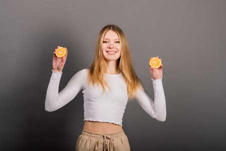 Smiling woman eating orange, half fruit, long hair. Studio shot