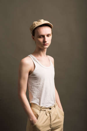 Androgynous young man in men outfit indoors. Studio shot