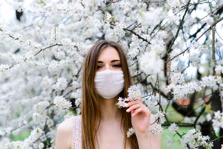 Close up portrait of tender girl in a white blouse under a blossoming cherry tree with a mask with flowers