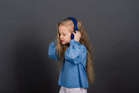 Smiling little girl in headphones on a grey background. The child listens to music, plays and learns online. Electronic digital training.