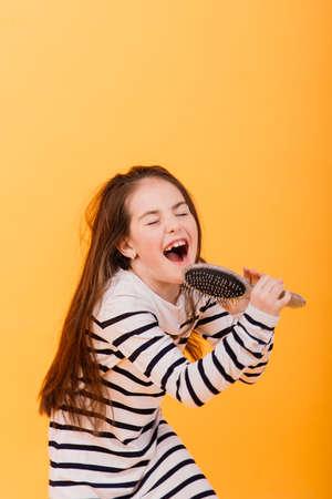 Pretending superstar, small girl listening music. Musical education, singing hairbrush mic and developing voice.