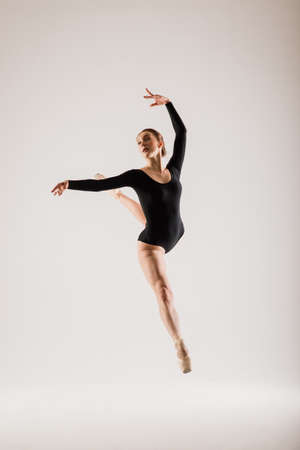 Portarit of Sensual professional caucasian callet dancer in body suit and pointes shoes posing on floor on white.