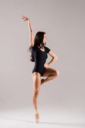 Flexible female, ballet dancer in black bodysuits, ballerina