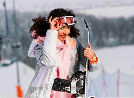 Young african woman on ski, winter sport snowboarding concept wearing gogglees, healthy