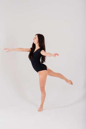 Portrait of a female, dancing ballerina in a black bodysuit in the Studio on gray background