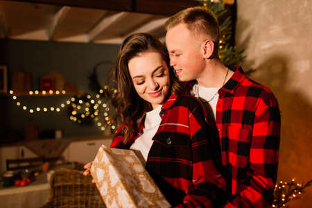 Love, christmas, couple, proposal and people concept. Happy man giving diamond engagement ring to woman at home