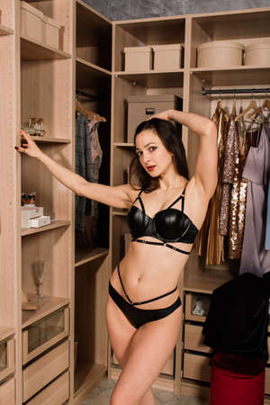 Shapely seductive woman in a white and black lingerie standing in cloakroom, near wardrobe, bathroom