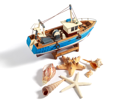trawler net: Model fishing boat with shells and starfishes on the white background