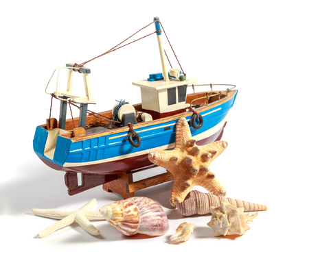 Model fishing boat with shells and starfishes on the white background