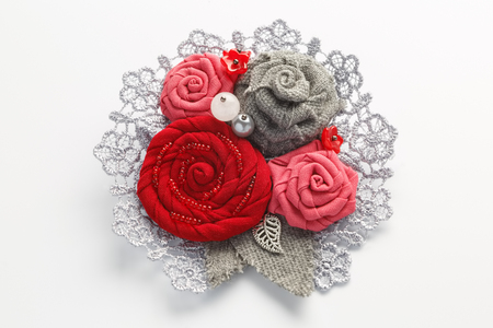 Stylish handmade brooch consisting of red flowers from fabric on a white background Stock Photo