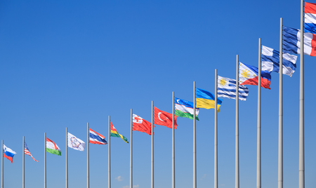 Flags of many countries flutter on the background of the blue sky in sunny day
