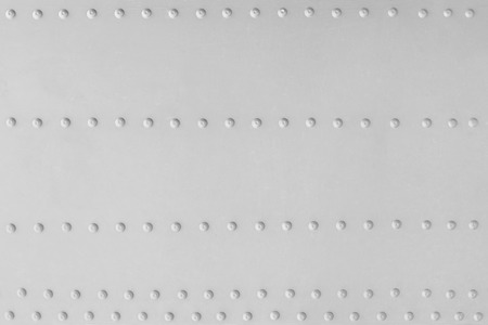 Aluminum plate with several rows of rivets as a background