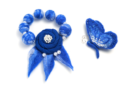 Blue bracelet and brooch in the form of a butterfly handmade on a white background
