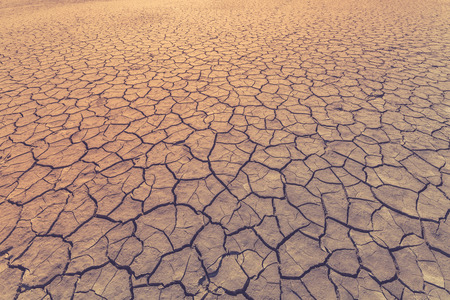 Land is covered with cracks as a symbol of drought, extreme weather conditions or as a background. Toned image