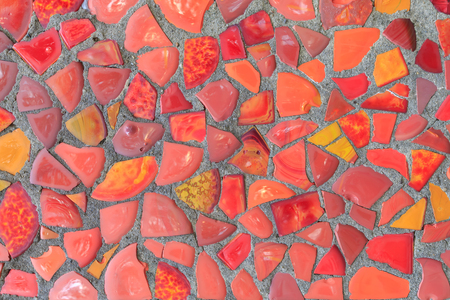 The fragment of the wall is decorated in red mosaic of different shades as a background or a backdrop