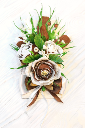Artificial flowers handmade as decoration of a greeting card on a white wooden background