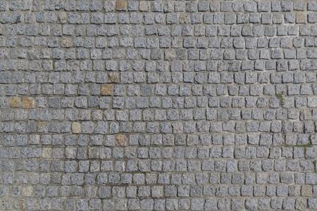 De weg is geplaveid met granieten stenen met een vierkante vorm als achtergrond of achtergrond Stockfoto