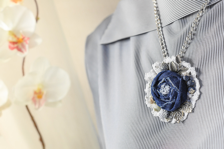 Pendant handmade in the form of a flower of denim on the background of a striped female blouse