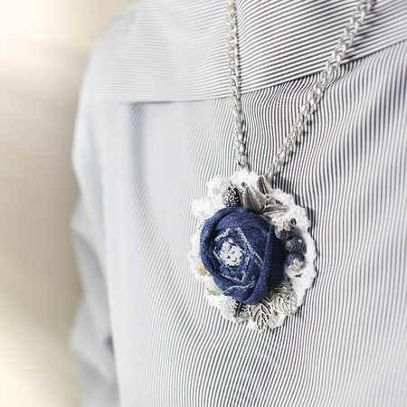 Pendant in the form of a flower of denim as a stylish accessory of a woman
