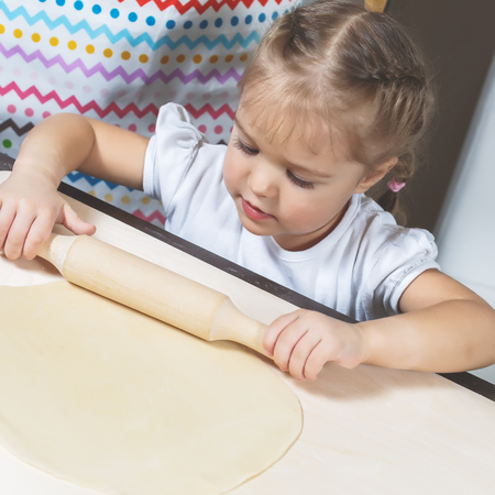 A little girl rolls out the dough using a wooden rolling pin at home