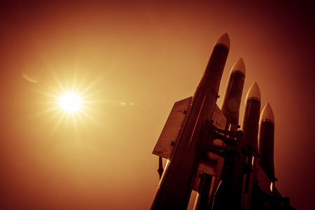 Four rockets of anti-aircraft missile system are directed upwards against a background of bright sun. Orange toned image