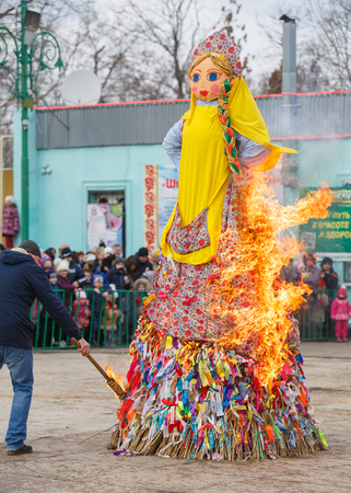 TAGANROG, RUSSIA, 26 FEBRUARY 2017: Maslenitsa celebration. Man sets fire to a big doll-scarecrow on a stage in a city park