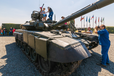 KADAMOVSKIY TRAINING GROUND, ROSTOV REGION, RUSSIA, 26 AUGUST 2017: International military technical forum ARMY-2017. Photographer shoots young visitors of the exhibition on the tank T-90A