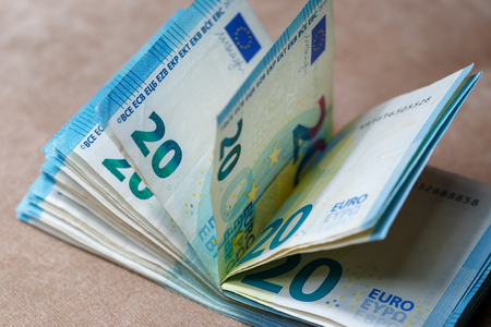 Bundle of money worth 20 euros on a light brown background