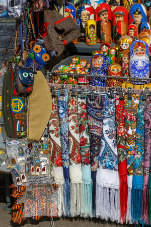 Russian souvenirs such as colorful shawls, scarves, painted matryoshkas, decorative small bags, purses and military headgear lie on the counter and wait for foreign tourists Editorial
