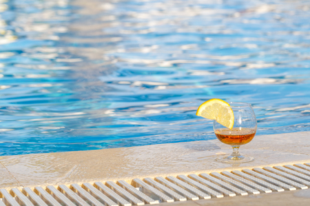 Glass of cognac, a slice of lemon, blue pool water as an attribute of a luxurious holiday