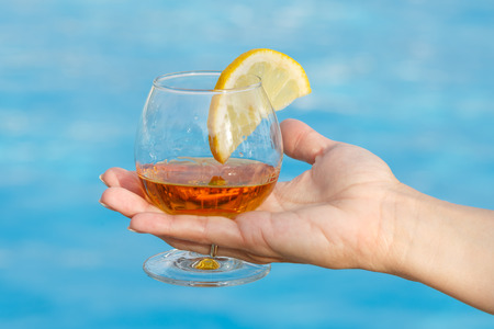 Glass of fragrant cognac with a slice of lemon in a womans hand on a blue background