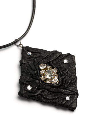 Black leather pendant with precious stones in the shape of a lozenge on a white background