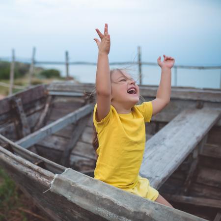 Portrait of a joyful girl sitting on an old boat on a summer evening