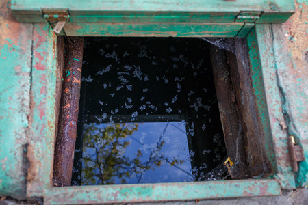Old, rusty, metal well with dirty water. View from above