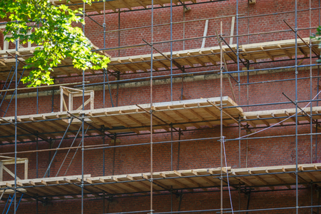 Scaffolding, with wooden floors, near brick wall
