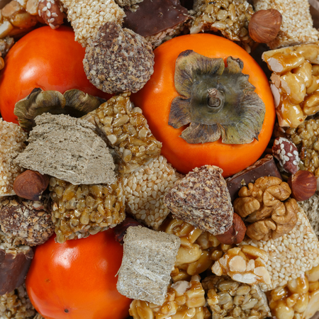 Halva, sesame snaps, nuts, chocolates and persimmons close up as background or backdrop