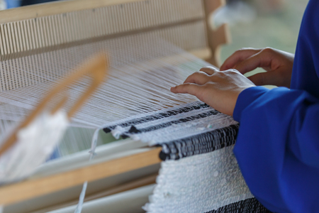Young woman weaves a white cloth on a wood loom. Traditional Russian folk art