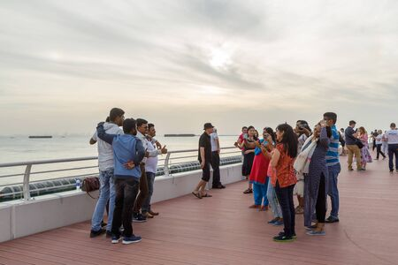 DUBAI, UAE, JANUARY 13, 2019: Smiling and happy tourists are photographed on the waterfront in the evening