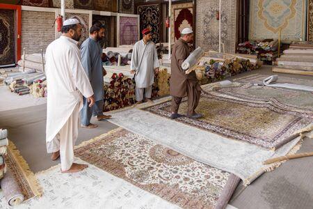FUJAIRAH, UAE, JANUARY 11, 2019: Sellers show exquisite carpets