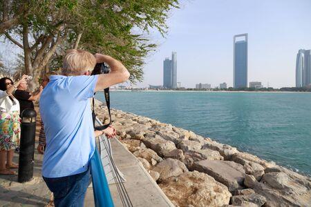 ABU DHABI, UAE, JANUARY 10, 2019: Tourists photographs a beautiful cityscape on a warm sunny day