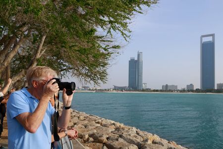 ABU DHABI, UAE, JANUARY 10, 2019: Tourist photographs a beautiful cityscape on a warm sunny day