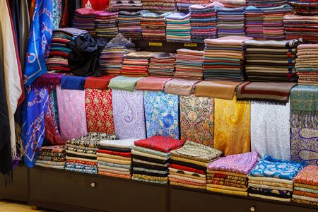DUBAI, UAE, JANUARY 13, 2019: A lot of beautiful handmade pashmina shawl are on the shop counter Redactioneel