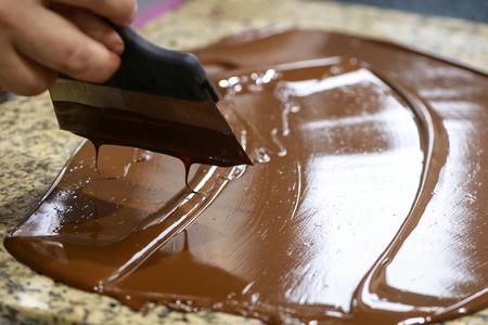 Chocolatier rührt die temperierte flüssige Schokolade um Standard-Bild